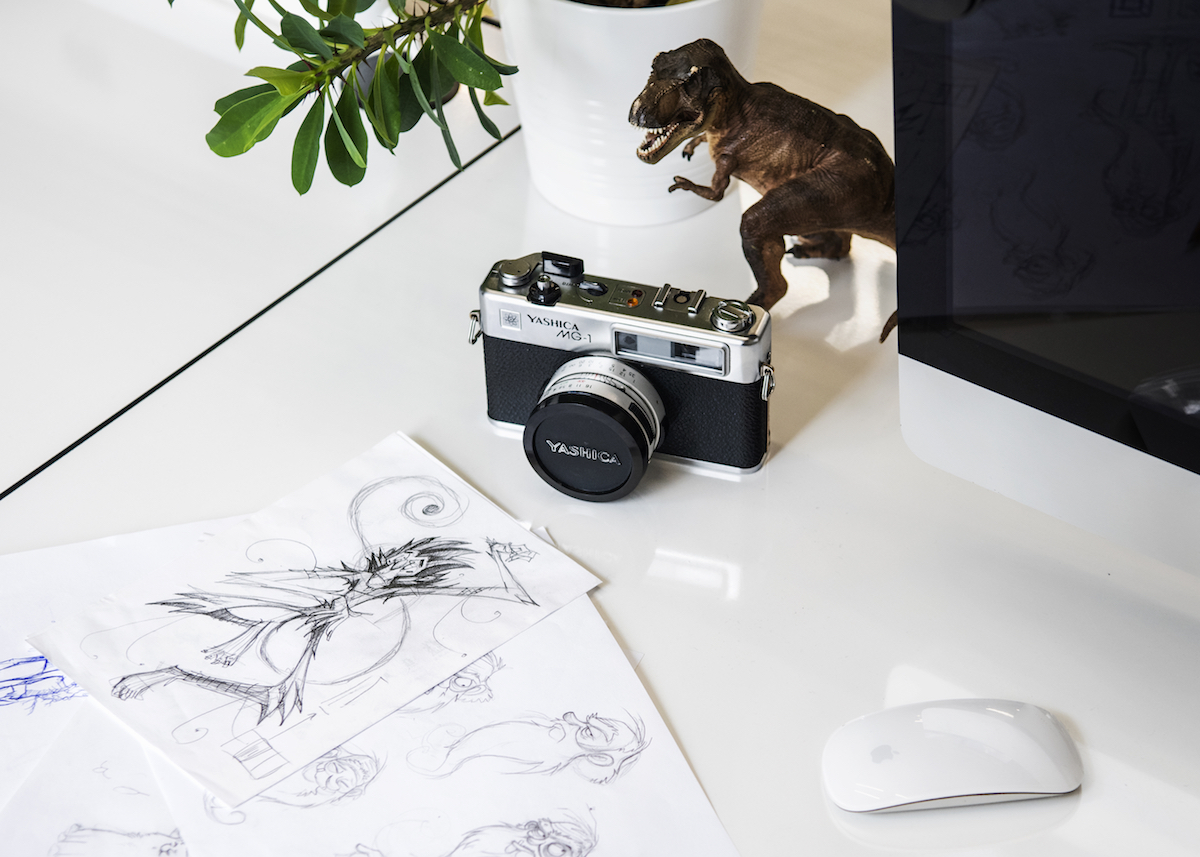 A dinosaur toy, sketches and a camera in Despark office