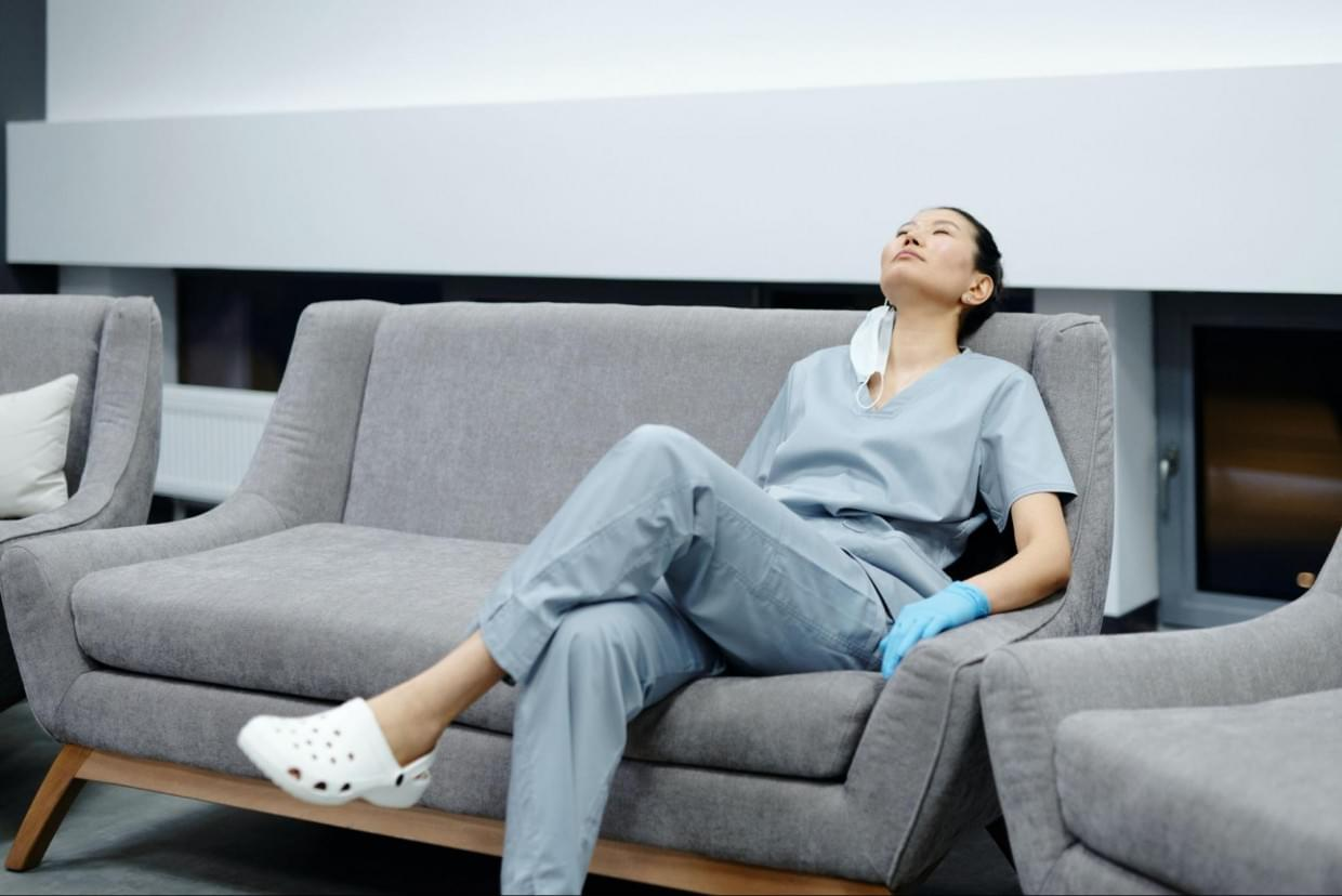A female nurse resting on a couch in a hospital